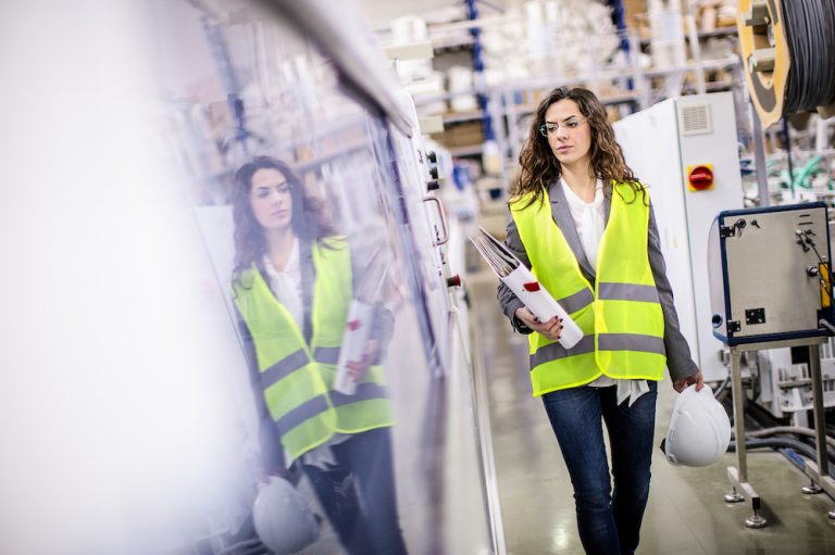 Young female worker walking through the factory