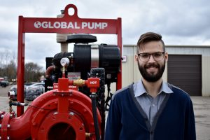 Joe Cherluck next to Mersino 8GSH pumps at their manufacturing facility in Davison, MI.