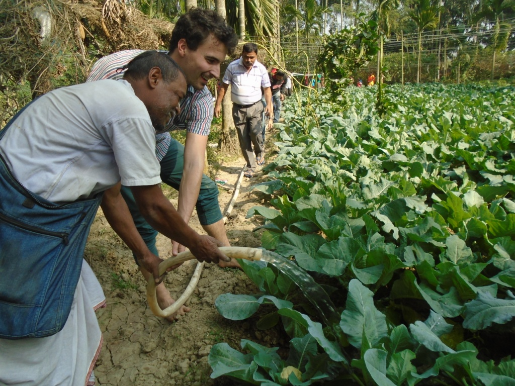 Kevin Simon waters some vegetables with Siddheswar, a farmer collaborating with Khethworks.