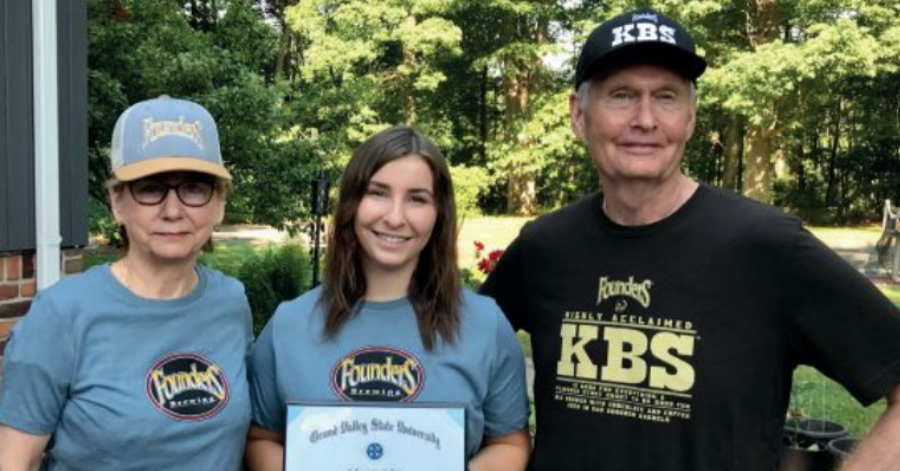Kasey with her grandparents in Founders gear, celebrating her degree, graduation, and signing with Founders.